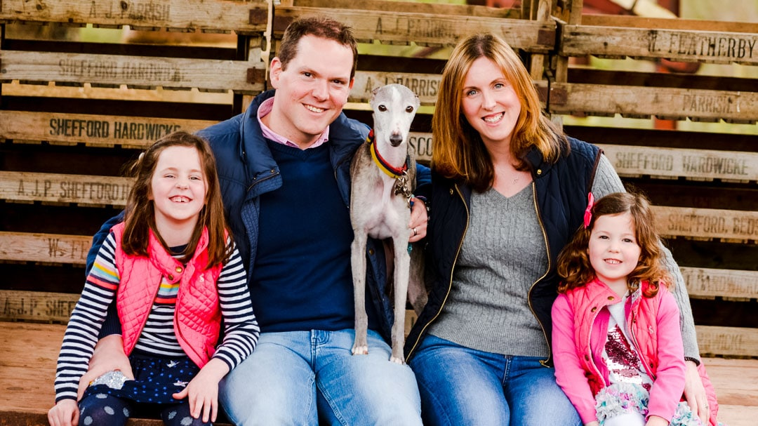 Family photo with dog sitting on farm trailer during family photo session on farm in Worcestershire by Michelle Morris