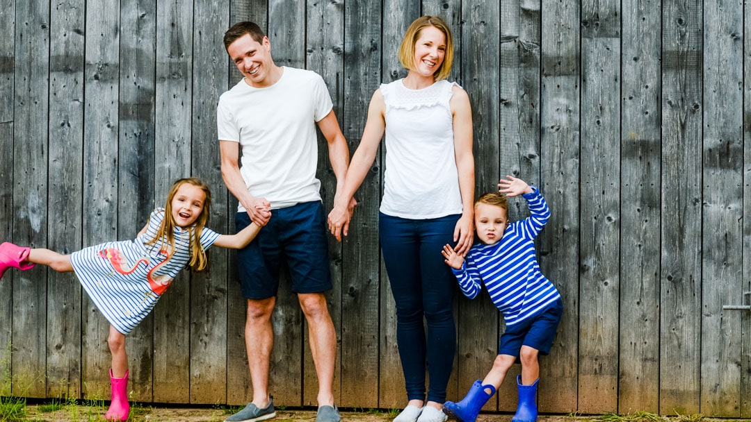 Fun family photo in front of farm door in summer by Michelle Morris