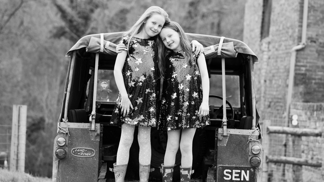 Sisters standing on Land Rover during summer photo session on farm by Michelle Morris Worcestershire