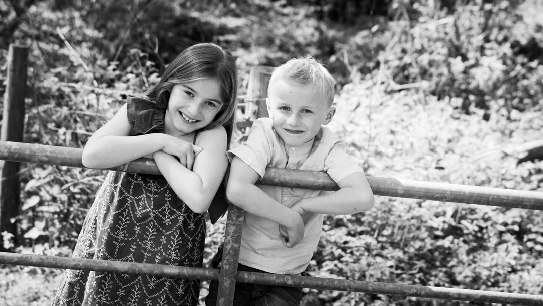 Brother and sister standing on fence summer photo session on farm in Worcestershire