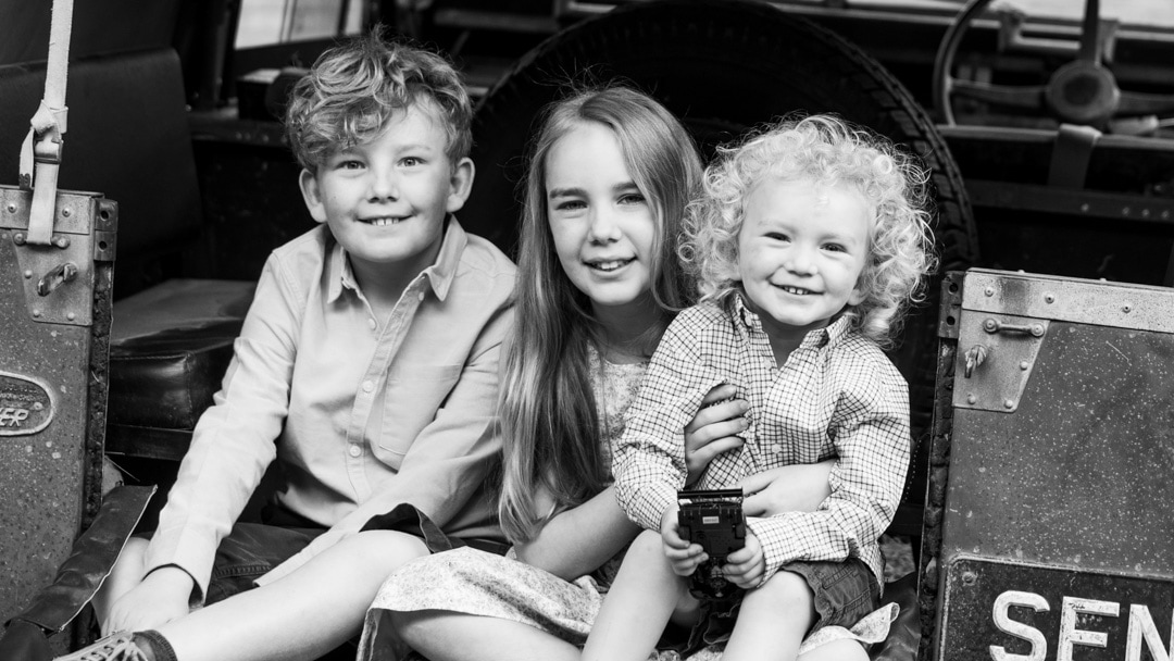 Siblings photo taken on a Land Rover during family photo session on farm in Worcestershire by Michelle Morris