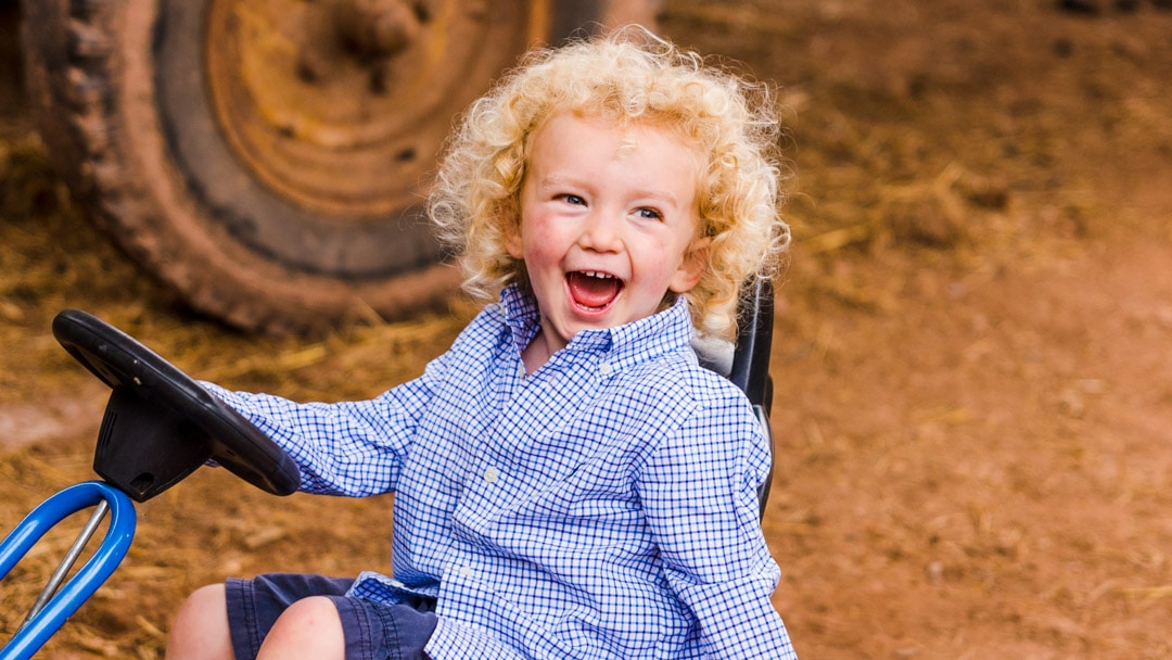 Little boy giggling during family photo session on farm in Worcestershire by Michelle Morris