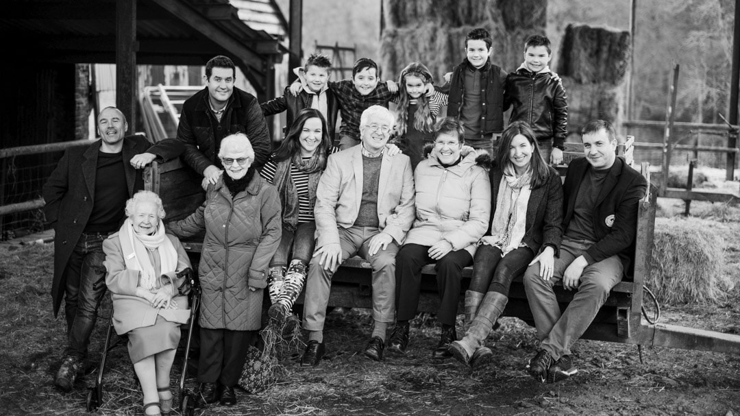 Big family photograph with four generations sitting on trailer on farm by Michelle Morris in Worcestershire